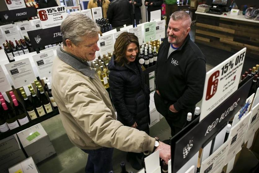 North Andover, MA--1/5/2019--Gov. Charlie Baker (left) and Lt. Gov. Karyn Polito (center) are shown a selection of wine in Wine ConneXtion during a tour of local businesses in North Andover, MA Saturday afternoon. (Nathan Klima) Topic: 06lawrence Reporter: Laura Crima
